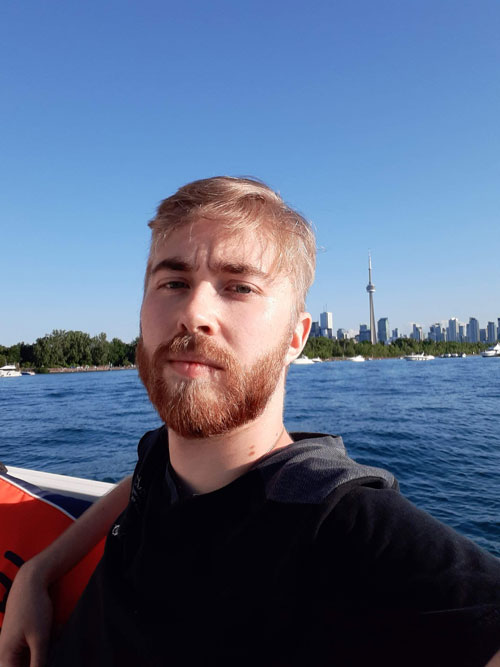 Toronto SEO Expert, Johnny Baskin, sitting in a boat with the Toronto Skyline and CN tower behind him.